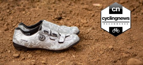 A pair of Shimano RX8 Gravel Shoes on muddy ground, overlaid with a 'recommends' badge