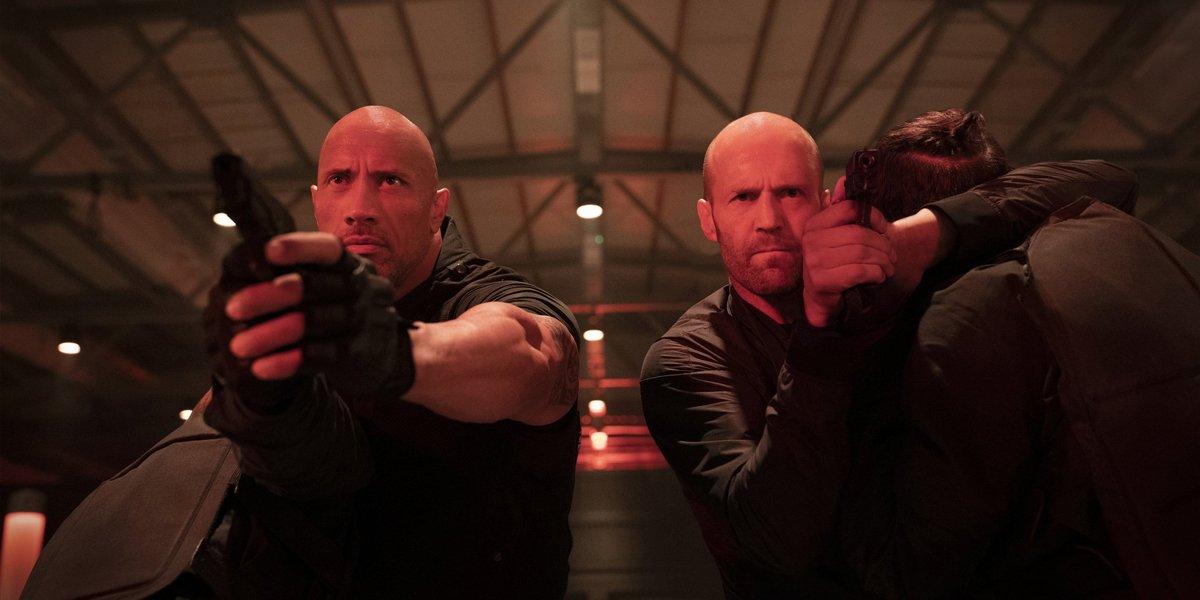 Hobbs (Dwayne Johnson) and Shaw (Jason Statham) aim guns in Hobbs & Shaw