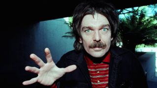 Captain Beefheart staring at the camera with his open hand raised
