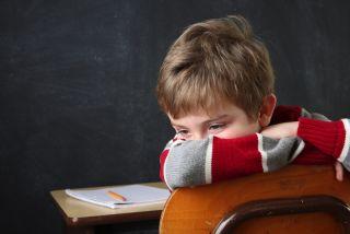 A boy slumps at his school desk, hiding his face.