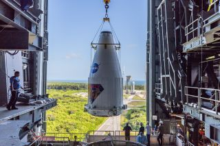 The Lucy spacecraft enclosed in its fairing being lifted onto its rocket in preparation for launch.