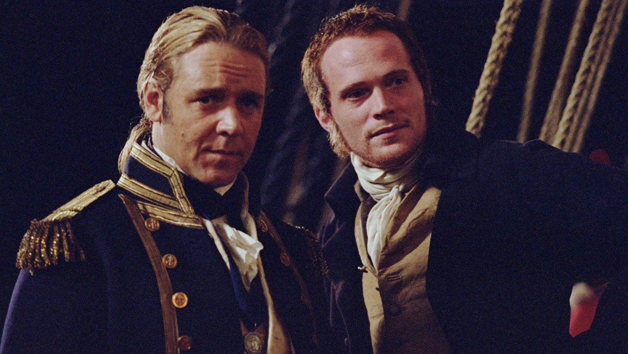 Russell Crowe and Paul Bettany standing together on their ship in Master and Commander.