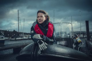 Nicola Walker in character as Annika, standing in a powerboat in the harbour wearing a navy windbreaker and a red lifejacket