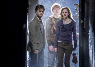 Daniel Radcliff, Rupert Grint and Emma Watson stand in a doorway