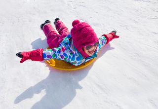 A little girl goes sliding down a snowy hill on a saucr