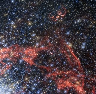 A new image taken with the Hubble Space Telescope shows the supernova remnant SNR 0509-68.7, also known as N103B. It's the wispy, elongated shell of red gas and dust near the top of the image.