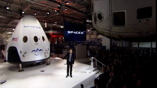 Elon Musk unveils the Dragon V2 space capsule on May 29, 2014, during a press briefing at the SpaceX headquarters in Hawthorne, California.