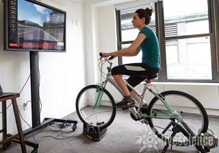 a woman is riding an indoor bike.
