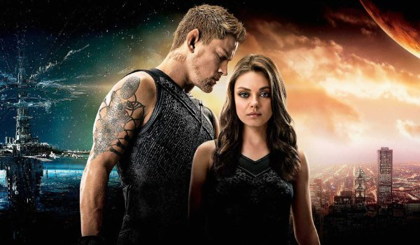 Jupiter Ascending Mila Kunis and Channing Tatum stand close in front of a sci-fi landscape