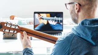 Man with an acoustic guitar takes an online guitar lesson