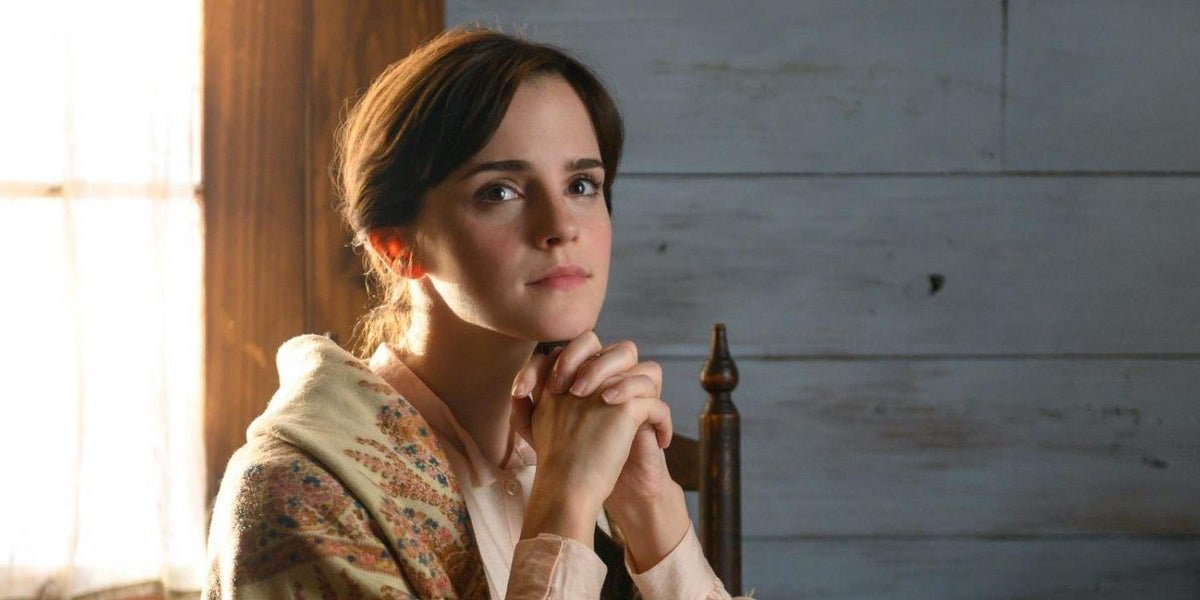Meg March (Emma Watson) sits with her hands folded under her chin in 'Little Women'