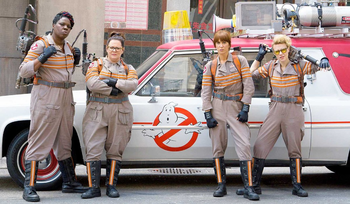 Ghostbusters 2016 lineup standing in front of the Ecto-Mobile