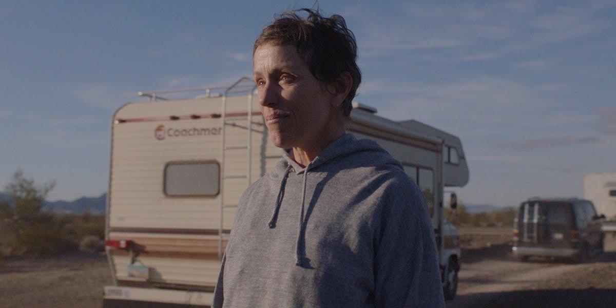Nomadland Frances McDormand stands alongside a caravan of vehicles