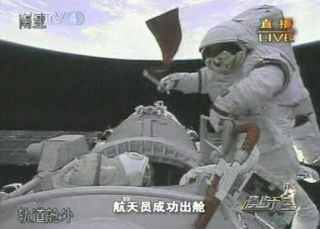 A Chinese taikonaut bears the flag of the People's Republic of China during the Shenzhou 7 mission's spacewalk on September 27, 2008.