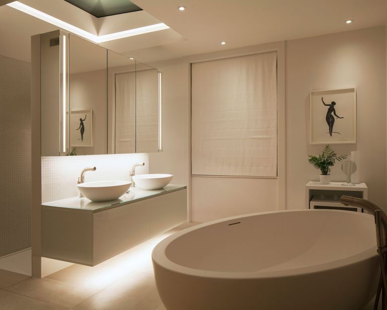 An example of bathroom lighting trends showing a white bathroom with lighting above a double vanity unit