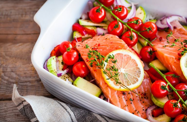 Best meal prep delivery services - Raw fresh delicious salmon, cherry tomatoes, onion, zucchini, pepper and lemon in pan, ready to cook