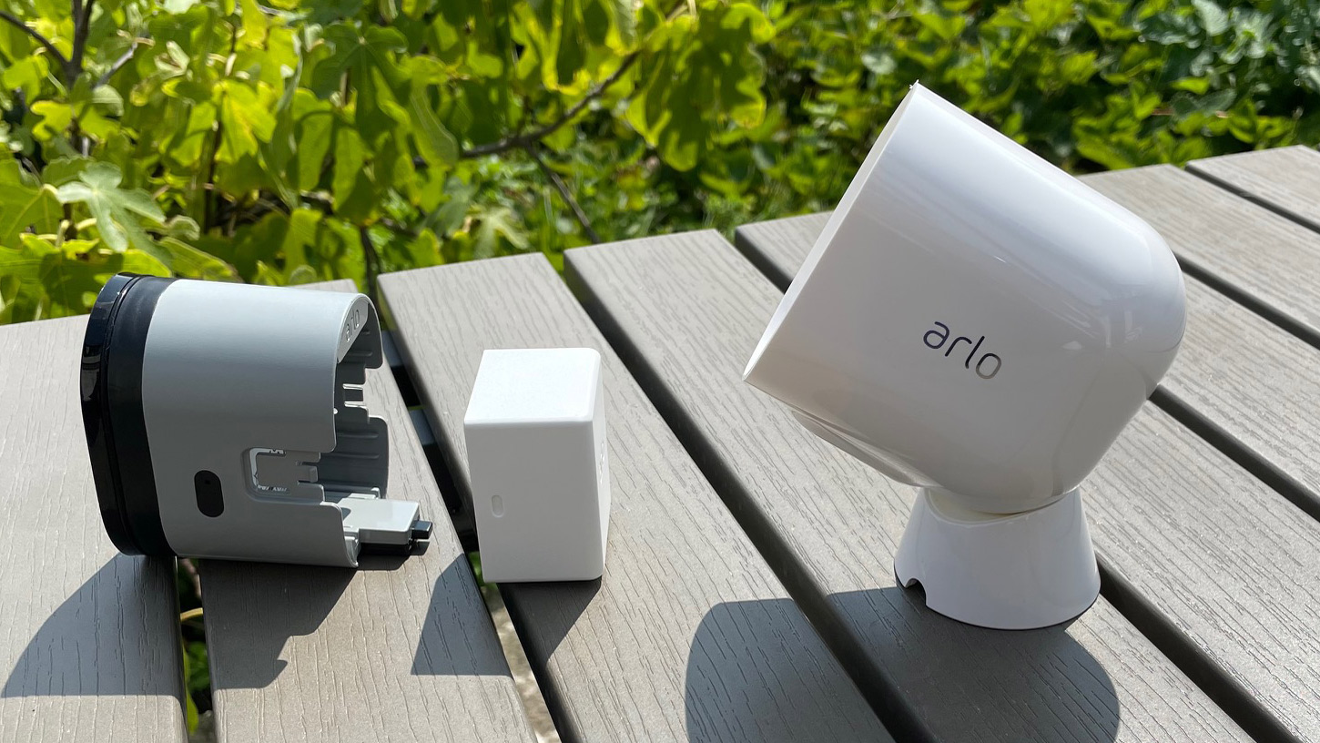 Arlo Pro 4 on a table in the garden with the casing and battery removed
