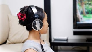 person wearing headphones in front of TV