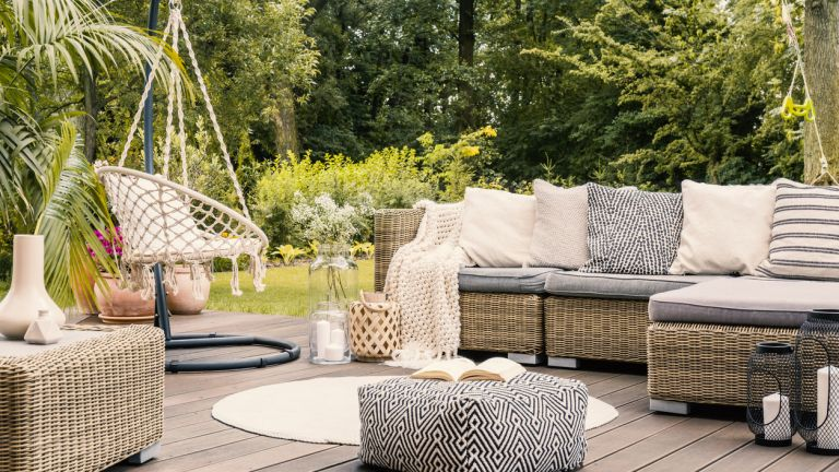 outdoor living scene with hanging chair and corner sofa