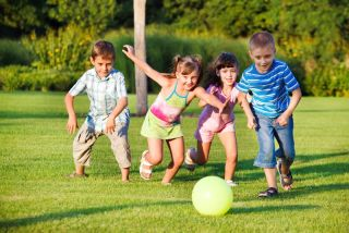 Children play and chase after a ball.