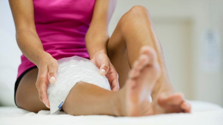 Woman ices her leg with an ice pack