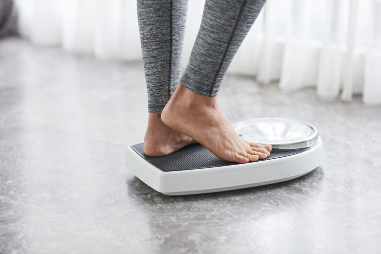 Winter weight gain: woman standing on scales