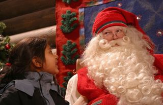 Kiasha Vekaria (6 years old) of Dartford, Kent, England, gazes at Santa Claus as she meets him in his office at Santa Claus village on the Arctic Circle near Rovaniemi, Finland on December 21, 2002.