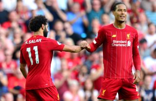 Liverpool's Mohamed Salah (left) celebrates scoring his side's second goal of the game with team-mate Virgil van Dijk during the Premier League match at Anfield, Liverpool.