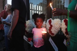 Six-year-old Mariah attends a memorial service with her mom in Dayton, Ohio, to recognize the victims of a mass shooting in the Oregon District there on Aug. 04, 2019.
