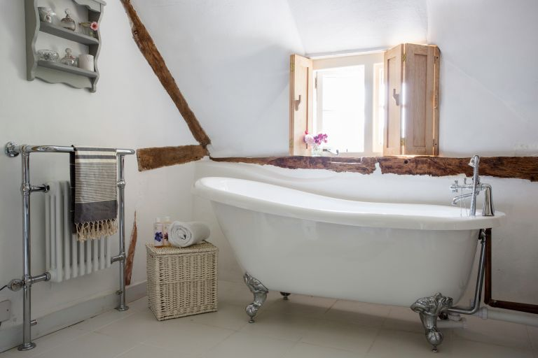 Traditional bathroom ideas with a roll-top slipper bath in listed thatched cottage with beams