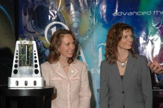 A prototype greenhouse sits next to U.S. Congress Rep. Gabrielle Giffords (left) and Jane Poynter, president and founder of Paragon Space Development Corporation (right). Paragon has teamed up with Odyssey Moon, a contender for the Google Lunar X Prize, t