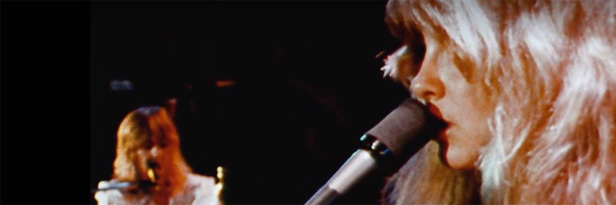 Christine McVie playing keyboards while Stevie Nicks sings.