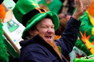 An unidentified man in a St. Patrick's Day parade waving at the crowd wearing a green leprechaun hat and laughing March 17, 2012, Cork, Ireland.