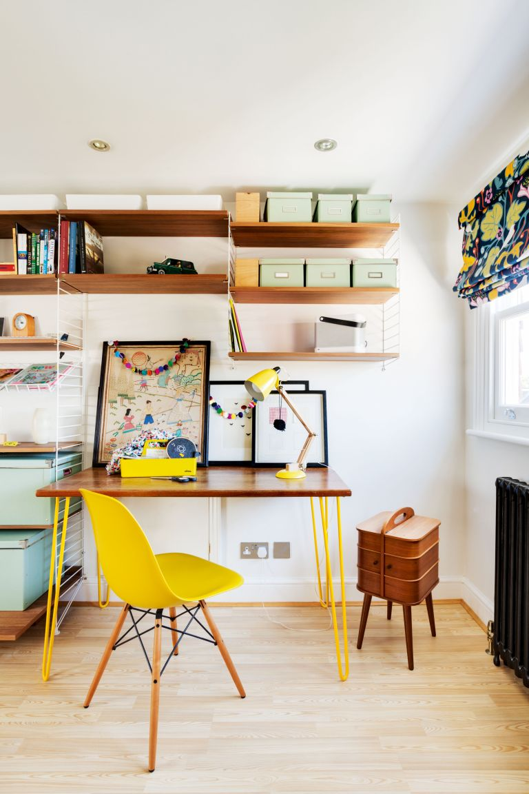 home office storage with wooden desk and bright yellow chair