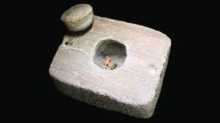 The stone box, its cap and contents: a figurine made of shell, representing a llama or alpaca, and a miniature gold arm band.