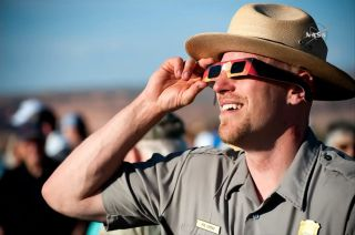 Park officer with solar eclipse glasses