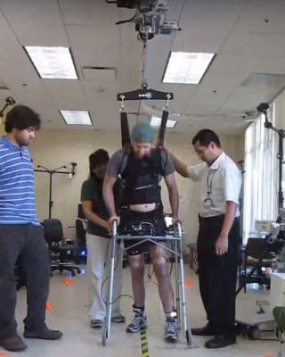 A man who was paralyzed in both legs for five years was able to use a brain-controlled system to walk again, along with a harness to help support his body weight.