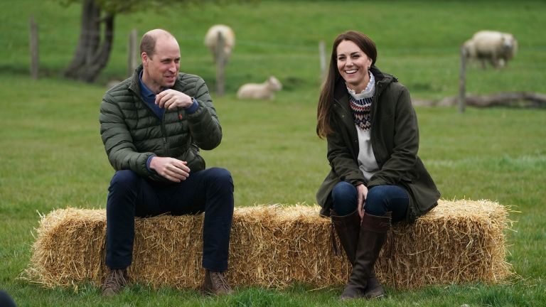 Catherine, Duchess of Cambridge and Prince William, Duke of Cambridge sit on hay balls during a royal visit to Manor Farm in Little Stainton, Durham on April 27, 2021 in Darlington, England