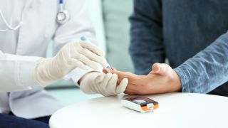 Gloved doctor pricks a patient's finger to conduct a blood sugar test