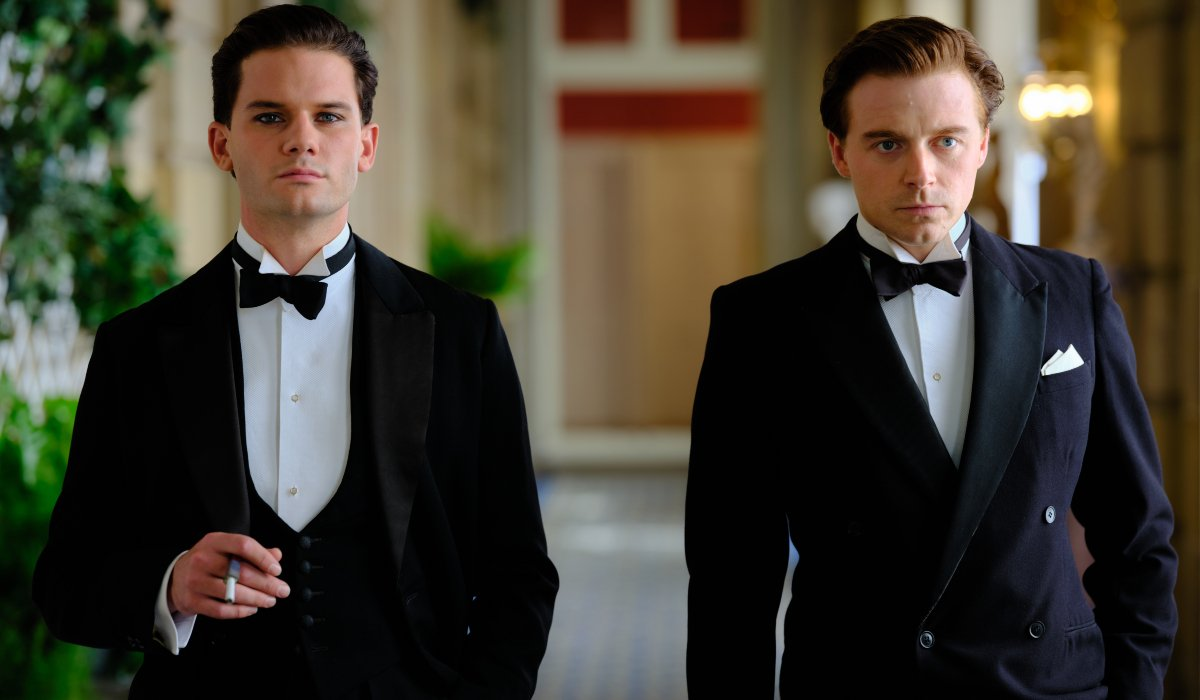 Jeremy Irvine and Jack Lowden walking down a hall in Benediction.