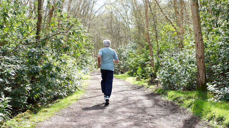 Older man runs through a green woodland path