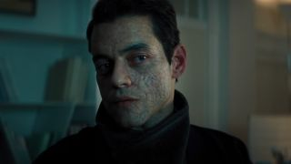 Rami Malek looks coolly towards the screen in No Time To Die.