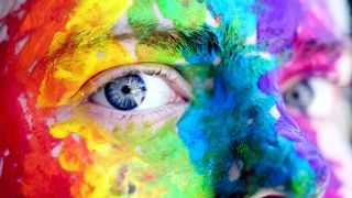 A woman bith blue eyes and colorful facepaint