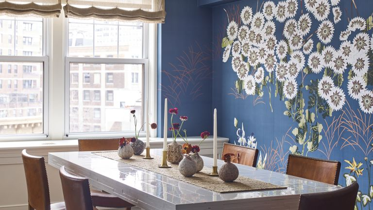 A dining room with deep blue mural wallpaper and vintage table and chairs