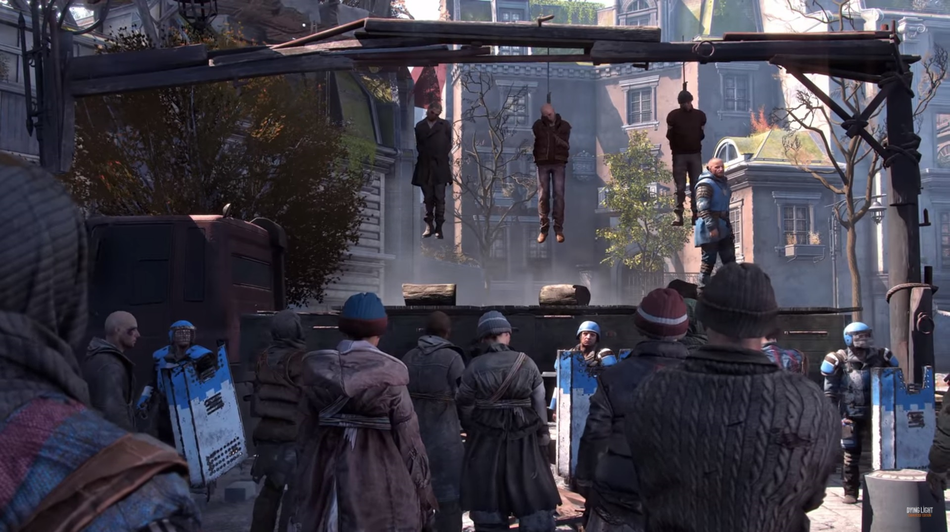 Dying Light 2 - Characters looking up at a gallows where three people and hanging.