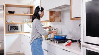 Vrouw die luistert naar een audioboek tijdens het koken