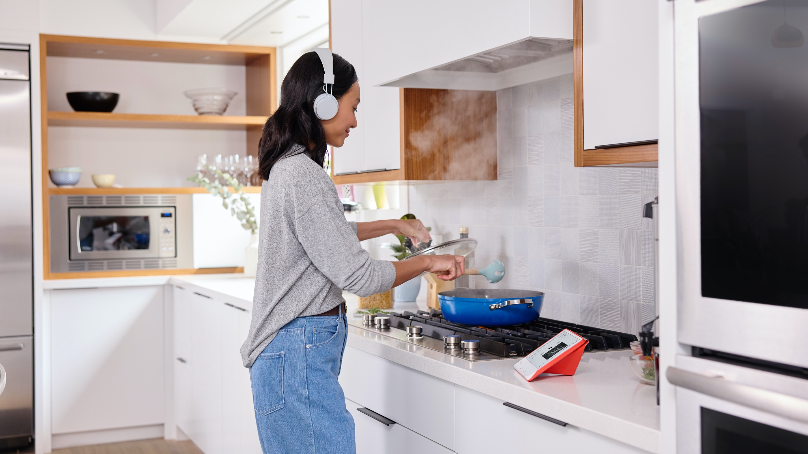 Woman wearing headphones while cooking and listening to audiobook