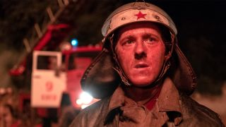 In a still image from the HBO miniseries 'Chernobyl,' a firefighter stares at the burning reactor building in the hours after the disaster began.