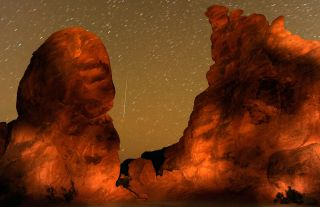A Geminid meteor streaks between peaks of the Seven Sisters rock formation early December 14, 2010 in the Valley of Fire State Park in Nevada. The meteor display, known as the Geminid meteor shower because it appears to radiate from the constellation Gemi