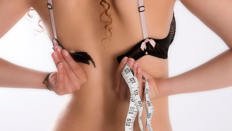 how to measure bra size: woman fastens her bra while holding measuring tape